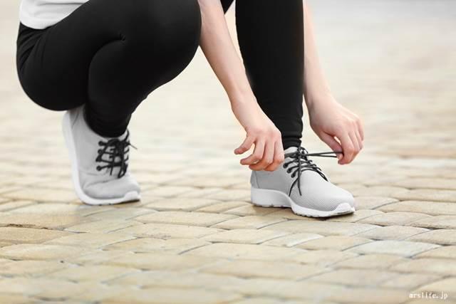 靴紐を結ぶ女性