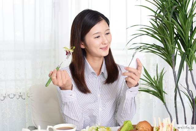 スマホをしながら食べる女性