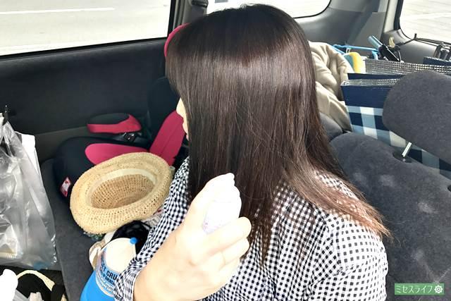 日焼け止めスプレーを髪に使う女性
