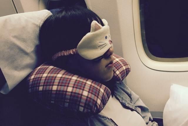 飛行機で寝ている女性