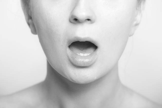 口を開く女性