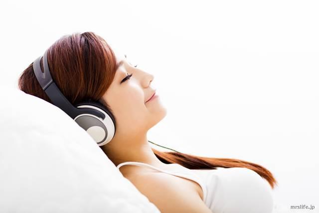 寝ながら音楽を聴く女性
