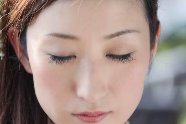 目をつぶっている女性