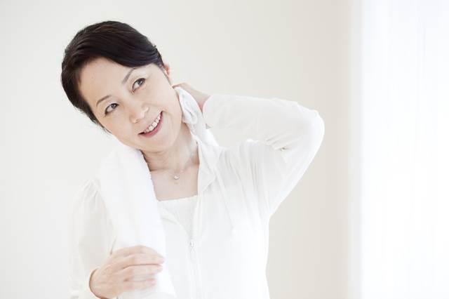 タオルで汗を拭いている女性